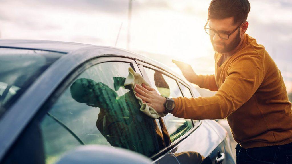 Homem limpando áreas do carro com uma caseira solução para limpar os vidros.